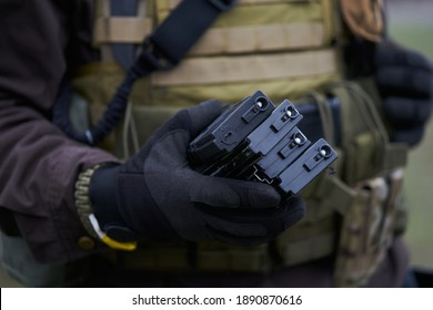 Airsoft player in protective gloves holds magazines for a machine gun in his hand