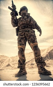 Airsoft player in U.S. army uniform, helmet, mask and glasses standing with service rifle replica in sandy area low angle, desaturated shoot. War games, military reenactment participant in desert