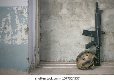 Airsoft rifle and protective helmet on the old concrete wall background with copy space. Sport weapon ammunition.