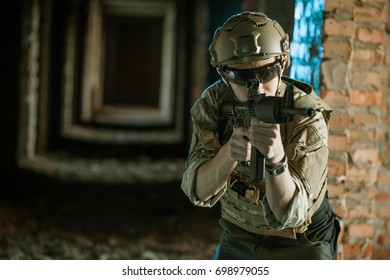 airsoft soldier with a rifle playing strikeball In an abandoned brick building