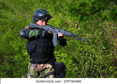 Airsoft soldier wearing a bulletproof vest with a gun in the forest.