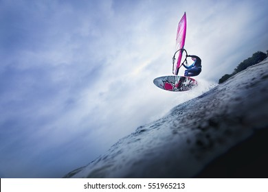 airtime of a windsurfer jumping over a big wave balancing in the sky