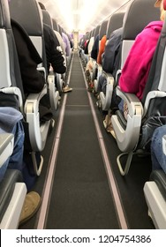 The aisle of a air plan, showing people seated but no one in the aisle