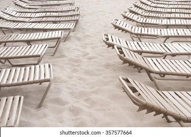 Aisle created by a row of empty, brown beach chairs on a sandy beach