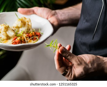 aiter serving roasted cauliflower with fresh herbs in his hand