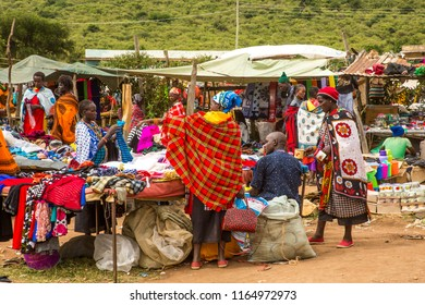 Aitong, Kenya - 6/7/2018:  Masai women shopping at a local masai open air market.  brightly colored clothing and many other items are for sale.