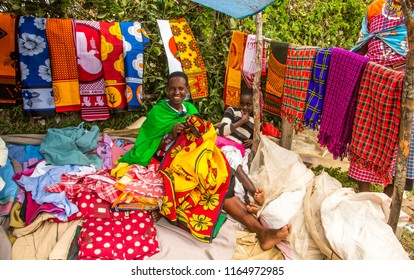 Aitong, Kenya - 6/7/2018:  Masai women selling brightly colored clothing at a local masai open air market.