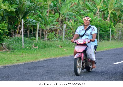 AITUTAKI - SEP 18 2013:Cook Islander woman rids motorbike. Aitutaki is the second most visited island of the Cook Islands.It has a population of approximately 2,000 people.