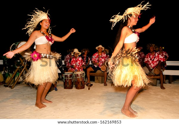 AITUTAKI - SEP 19 2013:Young adult Pacific Islanders women dancing Ura, a sacred ritual usually performed by a female who moves her body to tell a story, accompanied by intense drumming.