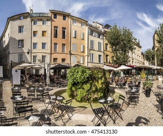 AIX EN PROVENCE, FRANCE - AUG 19, 2016: people enjoy the restaurant at the central market place with fountain covered by moss.