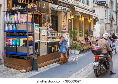 "AIX-EN-PROVENCE, FRANCE - AUGUST 14, 2015: Woman with dog buying crepes at street shop ""Bella Vita"". It's fast food restaurant selling pizza, crepes and icecream on streets of Aix-En-Provence."