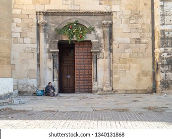 Aix-en-Provence, France - Dec 18th, 2018: Homeless lady sitting in front of Aix Cathedral, asking mercy from tourist.