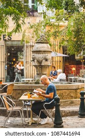 AIX-EN-PROVENCE, FRANCE - OCTOBER 9, 2009: Man reading and having meals in street cafe near fountain named Fontaine des Trois Ormeaux that dates back to 17th century