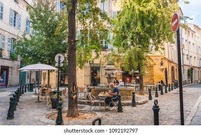 AIX-EN-PROVENCE, FRANCE - OCTOBER 9, 2009: People dining in cosy street cafe near fountain named Fontaine des Trois Ormeaux that dates back to 17th century