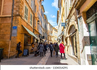 Aix-en-Provence, FRANCE, on March 8, 2018. People go along the street typical for small towns of Provence. Bright sunny spring day