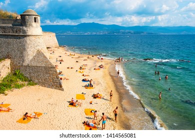 AJACCIO, FRANCE - SEPTEMBER 20, 2018: People sunbathing and bathing on the Saint Francois beach, the urban beach of Ajaccio, in Corsica, France, next to the citadel