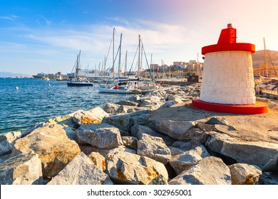 Ajaccio marina entrance pier with red and white lighthouse tower in a sunshine, Corsica island, France