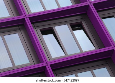 Ajar window with violet / purple frame. Colorful detail of office building exterior. Abstract tilt photo on the subject of contemporary architecture or modern business cityscape