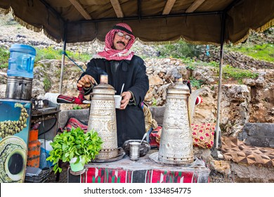 AJLOUN, JORDAN - March 2019: Bedouin man traditionally dressed preparing Bedouin mint tea in Ajloun, Jordan