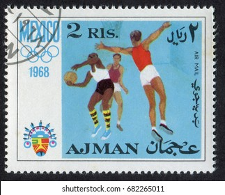 Ajman - CIRCA 1968. A postage stamp printed in the United Arab Emirates (UAE) shows jumping basketball gamers men, and a Mexican style mascot. From Mexico Olympic Games 1968 series, circa 1968