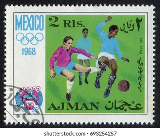 """Ajman - CIRCA 1968. A stamp printed in the United Arab Emirates (UAE) shows Football game, Mexico 1968. From """"Games of the XIX Olympiad in Mexico"""" series, circa 1968"""