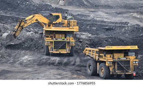 Ajmer, India - July 1, 2020 : Huge Dumper Earthmover Truck carrying minerals at an open pit quarry mines helped by a crane and other heavy machinery.