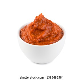 Ajvar or pindjur orange vegetable spread made from bell peppers, eggplants and oil. Marinara sauce, salsa, chutney or lutenica in white bowl isolated with clipping path