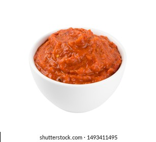 Ajvar or pindjur orange vegetable spread made from bell peppers, eggplants and oil. Marinara sauce, salsa, chutney or lutenica in white bowl isolated
