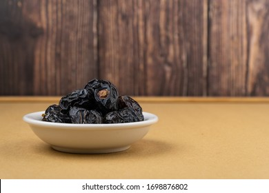 """Ajwa Dates or """"Kurma Ajwa"""" in a small plate isolated on wooden background. Prophet dates is one of the special fruit of Arabic ."""