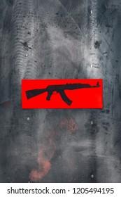 AK 47. Black Kalashnikov automatic rifle on red paper, on metal grunge background. Copy space.