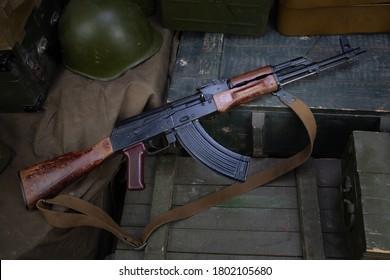 AK 47 gun with ammunitions on army green box background