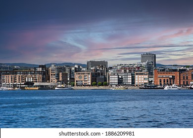 Akerbrygge district of Oslo with glowing cirrus clouds in the sky.