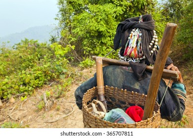 Akha villager carry things on her back in mountain, Laos