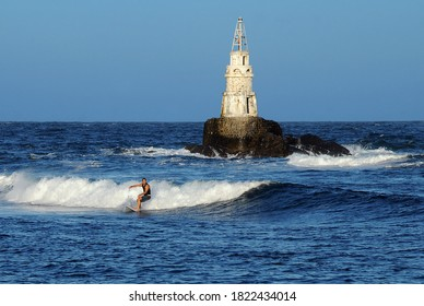 AKHTOPOL, BULGARIA - SEPTEMBER 16, 2020: Unidentified young surfer surfs waves in the Black sea near tiny lighthouse