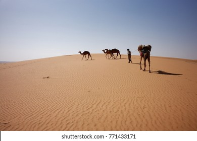 AKJOUJT, MAURITANIA - DECEMBER 1, 2017: a Moorish nomad leading his camels caravan in the desert, between Akjoujt and Atar, December 1, 2017.