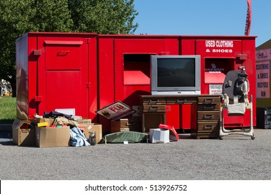 Akron, PA - October 5, 2016: A red, used clothing bin in a parking lot overflows with non-food donated household items.