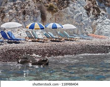 Akrotiri, Santorini, Greece. Sunbeds at the black Beach in Santorini.