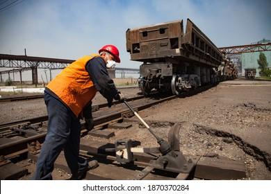 Aksu, Pavlodar region, Kazakhstan - May 29 2012: Metal alloys metallurgy plant. Railroad switchman in orange safety jacket on train car and blue sky background