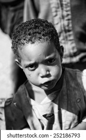 AKSUM, ETHIOPIA - SEP 28, 2011: Portrait of an unidentified Ethiopian cute little girl in old clothes in Ethiopia, Sep.28, 2011. People in Ethiopia suffer of poverty due to the unstable situation