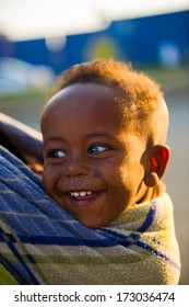 AKSUM, ETHIOPIA - SEP 30, 2011:Unidentified Ethiopian little cute happy boy is carried on his mother back in Ethiopia, Sep.30, 2011.Children in Ethiopia suffer of poverty due to the unstable situation