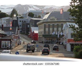 Akureyri, Iceland 09/01/2015 Street view with cars and traditional buildings and snow in the mountains in Akureyri city, north Iceland, Europe