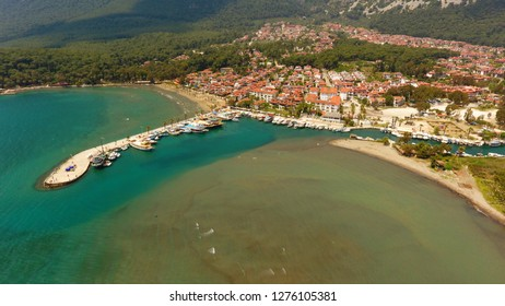 Akyaka beach in the centre of Akyaka village in Mugla province of Turkey, with Sakar mountains in the background, aerial view of city center.