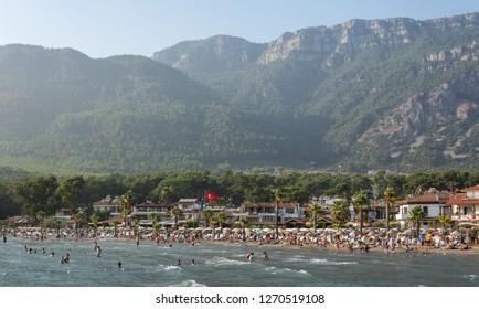 Akyaka, Mugla, Turkey - July 29, 2016. Akyaka beach in the centre of Akyaka village in Mugla province of Turkey, with Sakar mountains in the background, and people.
