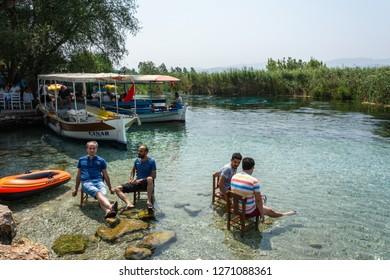 Akyaka, Mugla, Turkey - July 30, 2016. Azmak stream in Akyaka village in Mugla province of Turkey, with people and boats.