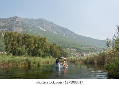 Akyaka, Mugla, Turkey - July 30, 2016. Tour boat on Azmak stream in Akyaka village in Mugla province of Turkey, with people.