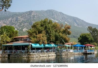 Akyaka, Mugla, Turkey - July 30, 2016. Restaurant along the Azmak stream in Akyaka village in Mugla province of Turkey, with people.