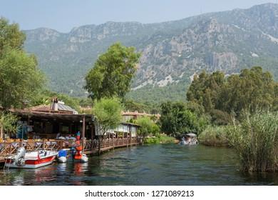 Akyaka, Mugla, Turkey - July 30, 2016. Azmak stream in Akyaka village in Mugla province of Turkey, with restaurant, boats and Sakar mountains in the background.