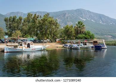 Akyaka, Mugla, Turkey - July 30, 2016. Azmak stream in Akyaka village in Mugla province of Turkey, with boats and Sakar mountains in the background.