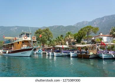 Akyaka, Mugla, Turkey - July 30, 2016. Boats on Azmak stream in Akyaka village in Mugla province of Turkey, with Sakar mountains in the background.