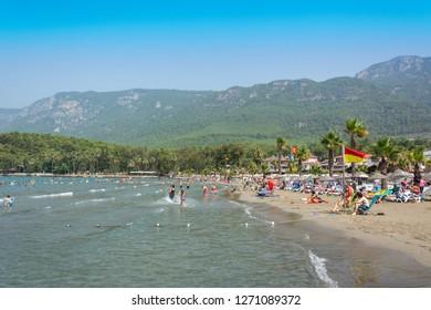 Akyaka, Mugla, Turkey - July 30, 2016. Akyaka beach in the centre of Akyaka village in Mugla province of Turkey, with Sakar mountains in the background, and people.